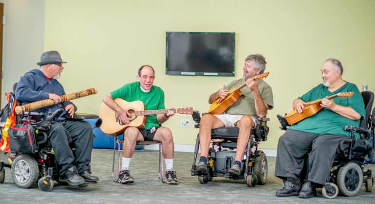 A group of disabled adult males are sitting and happily playing music together.
